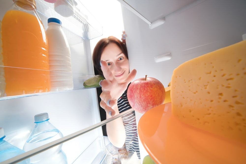 Funny,happy,girl,taking,apple,from,the,fridge.,view,from