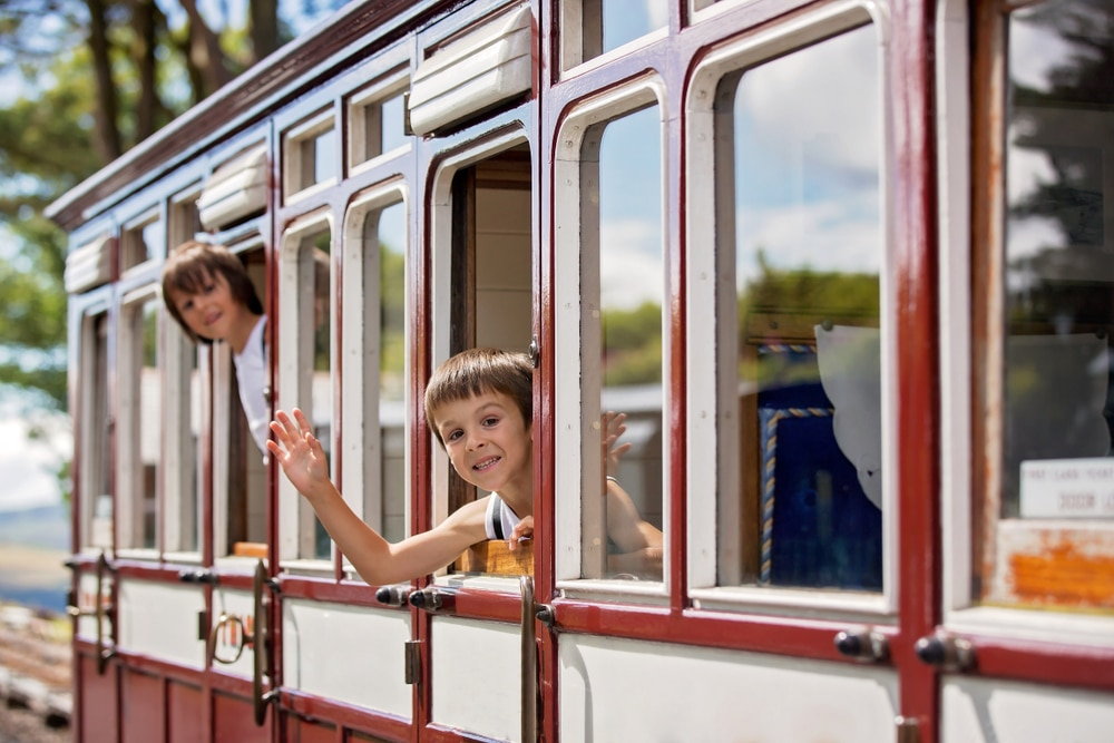 Beautiful,children,,dressed,in,vintage,clothes,,enjoying,old,steam,train