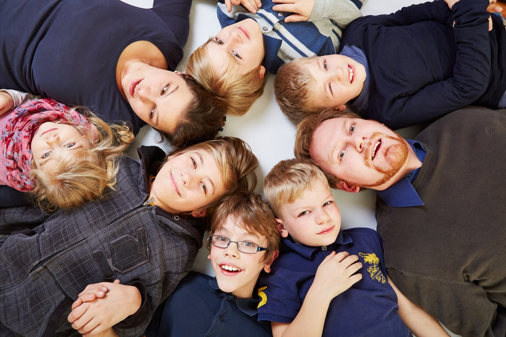 Big,family,with,six,kids,in,a,circle,looking,up