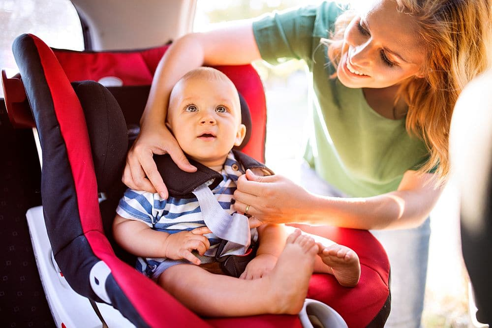 Young,mother,putting,baby,boy,in,the,car,seat.
