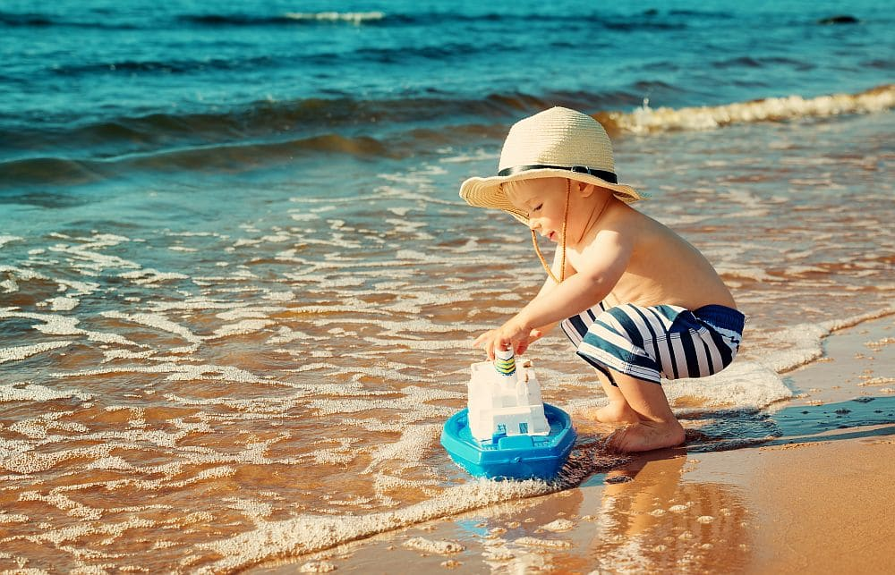 Baby,boy,playing,with,ship,toy,at,sea.,child,os
