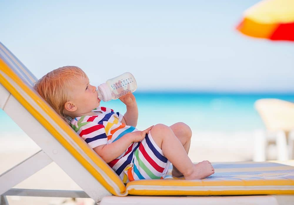 Portrait,of,baby,on,sunbed,drinking,water