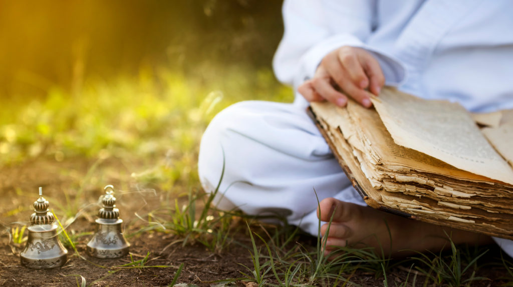 Buddhist,monk,sits,in,yoga,lotus,position,meditating,,reading,old