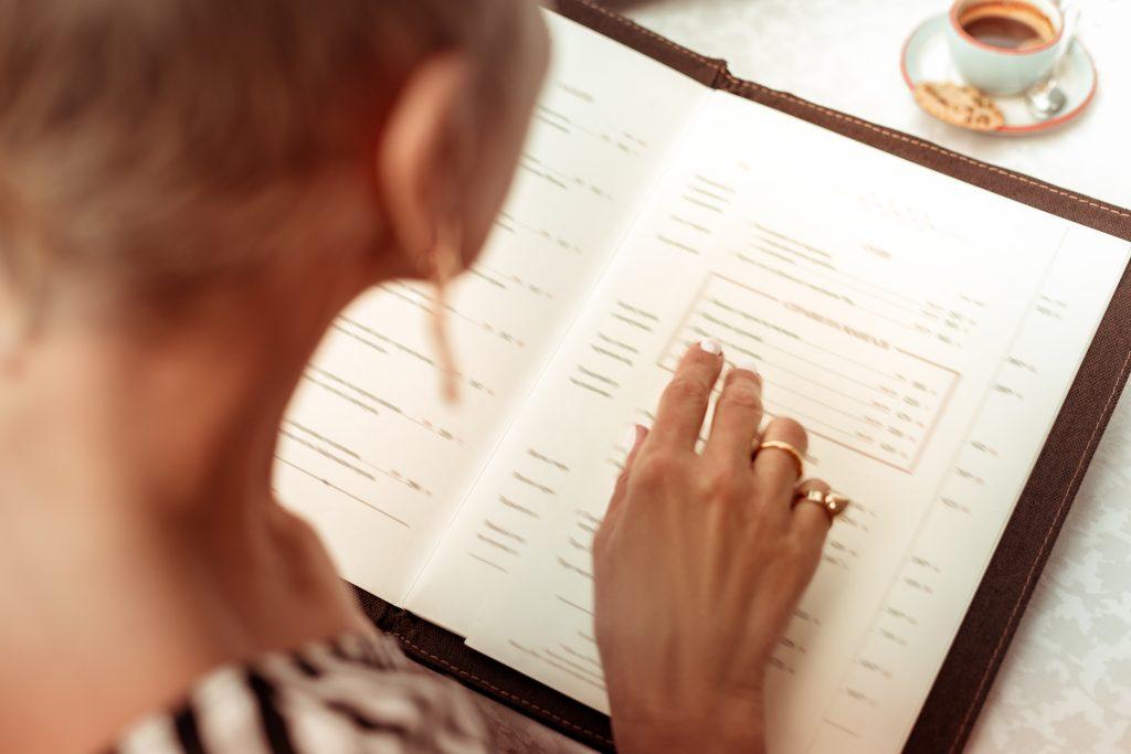 Reading,the,menu.,top,view,of,woman,wearing,nice,rings