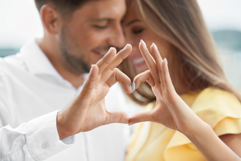 Beautiful,couple,in,love,making,heart,with,hands.,happy,smiling