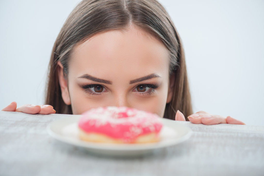 Beautiful,girl,is,looking,at,unhealthy,donut,with,appetite.,it