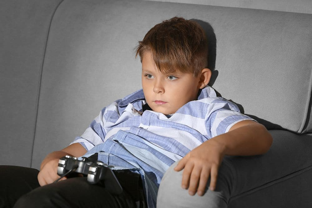 Overweight,boy,playing,video,game,at,home
