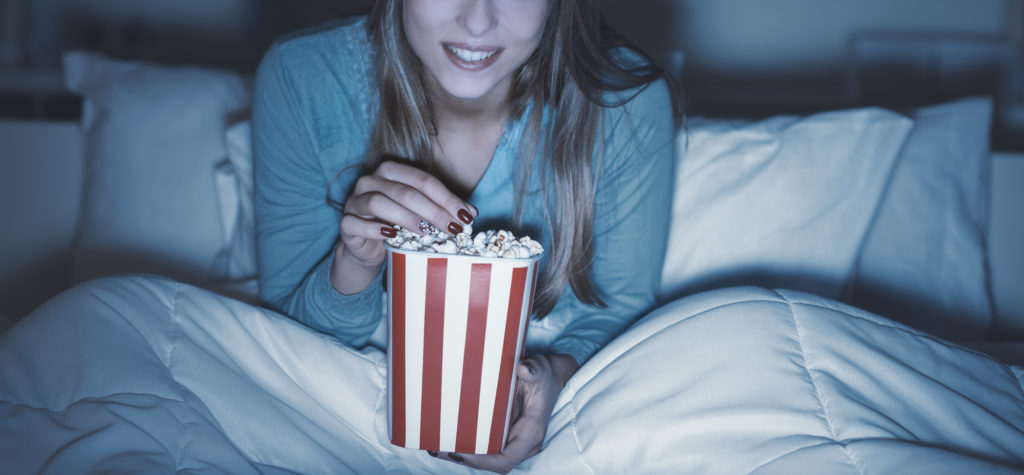 Happy,woman,relaxing,in,bed,and,watching,movies,on,tv