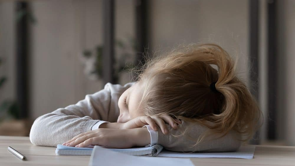 Close,up,tired,little,girl,sleeping,at,work,desk,,lying