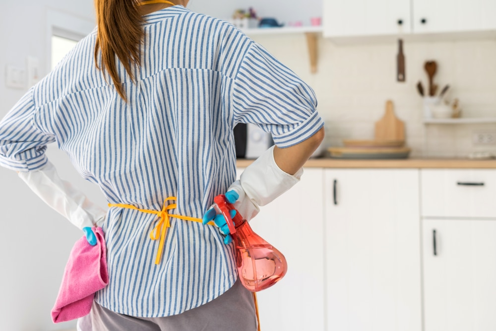 Tired,young,woman,standing,at,kitchen,room,with,cleaning,products