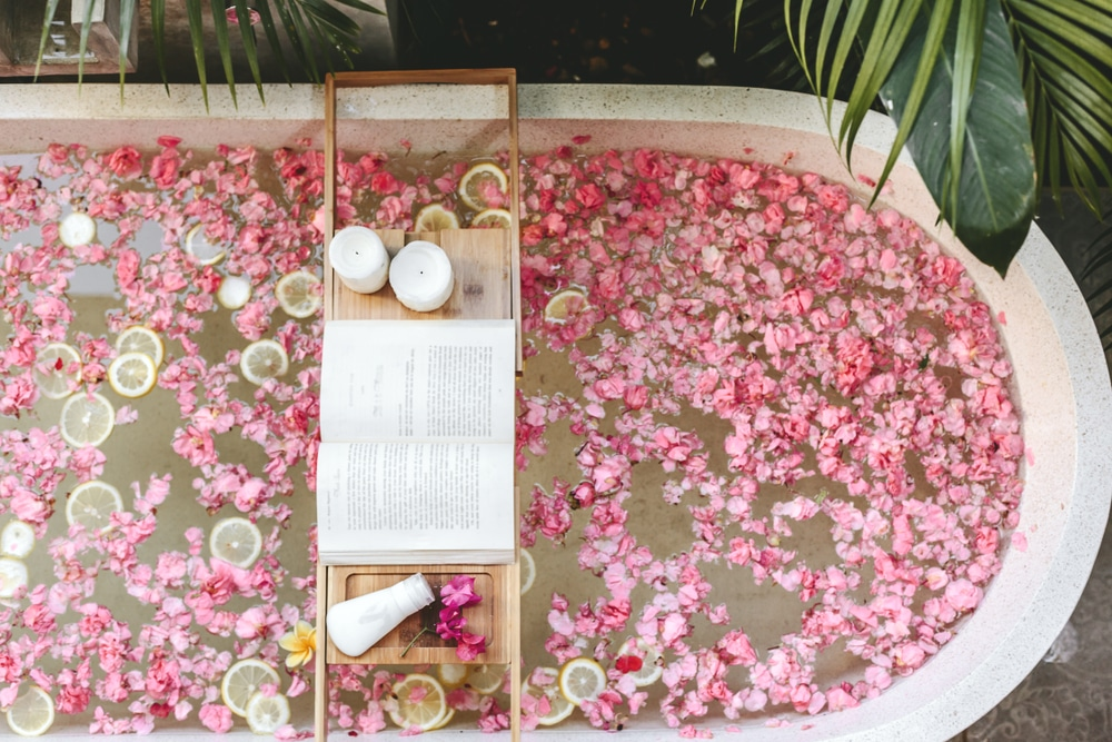 Top,view,of,bath,tub,with,flower,petals,and,lemon