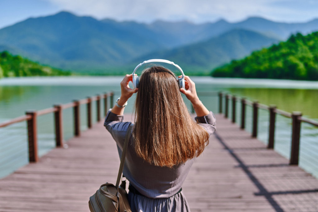 Girl,traveler,listening,to,calm,music,on,wireless,headphones,standing
