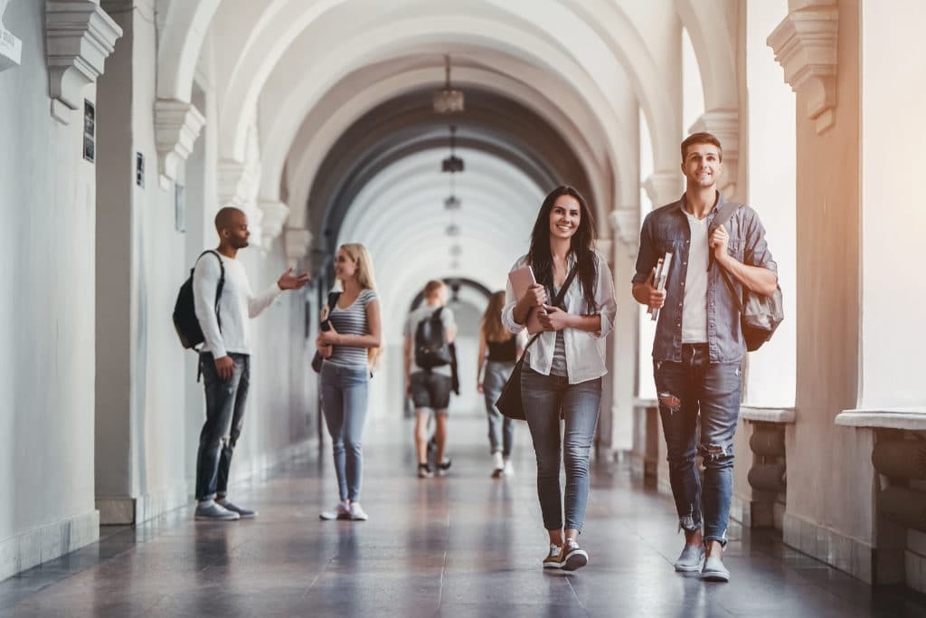 Multiracial,students,are,walking,in,university,hall,during,break,and