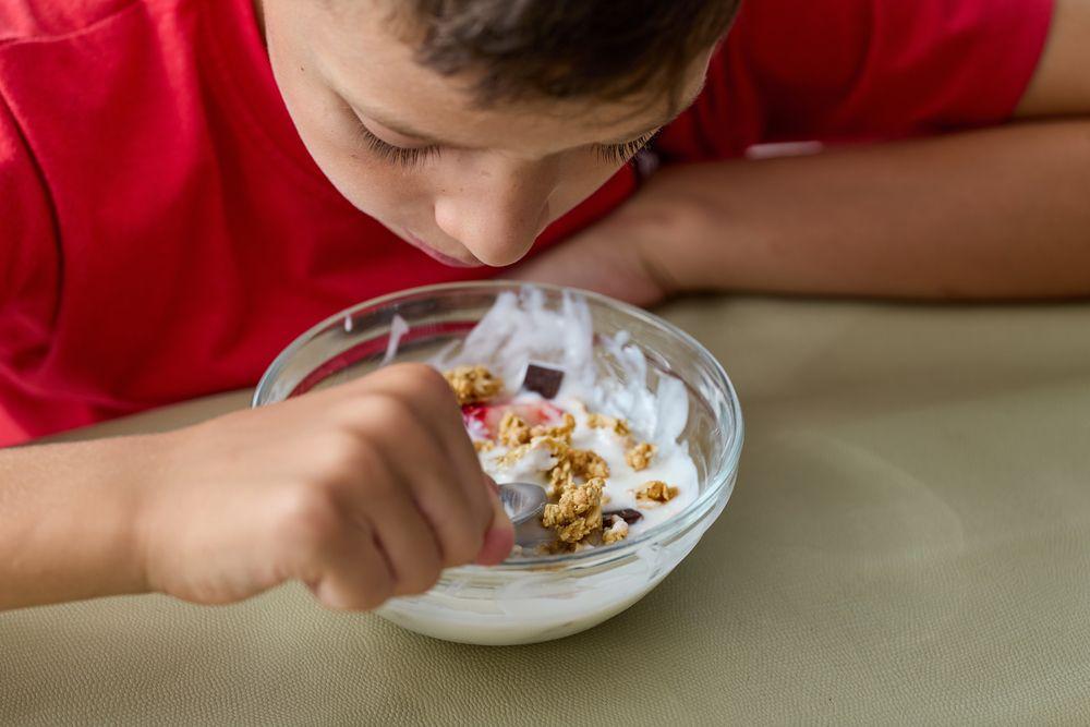 8,year,old,boy,eating,muesli,and,yoghurt,wearing,a