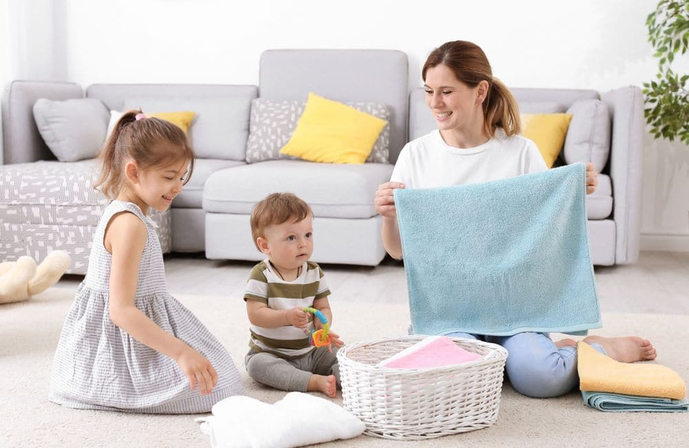 Housewife,with,children,folding,freshly,washed,towels,in,room