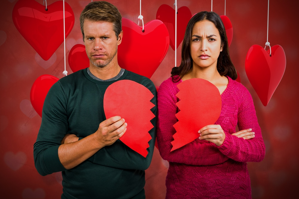 Portrait,of,serious,couple,holding,cracked,heart,shape,against,valentines